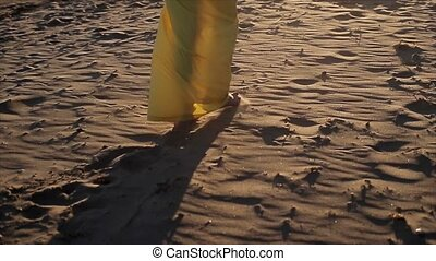 Woman in yellow dress walking on a beach barefoot at sunset