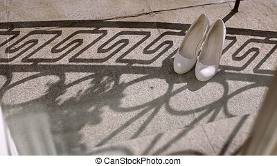 Woman's shoes on balcony at sunny day - White woman's shoes...