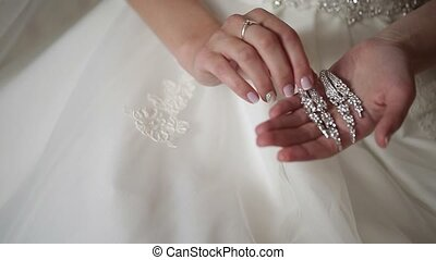 Bride holding earrings in hands closeup