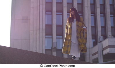 Female walking on city background - Female wearing yellow...