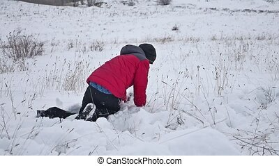 Teen boy rolling winter a ball of snow to build a fortress. sculpts snowman snow