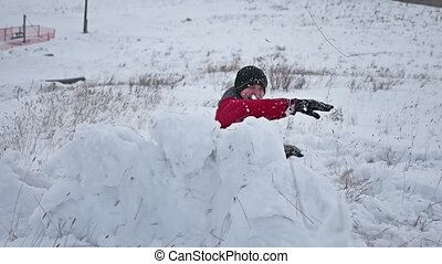 Teen boy rolling a ball of snow to build a snow fortress. sculpts snowman winter