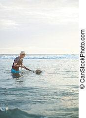 Man teaching dog to swim