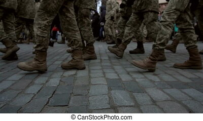 background with formation of soldiers in uniform marching on the pavement on the street