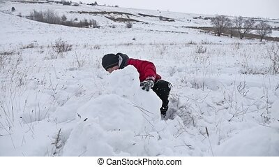 Teen boy rolling a ball of snow to build a fortress. snow...