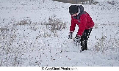 Teen boy winter rolling a ball of snow to build a fortress. sculpts snowman snow