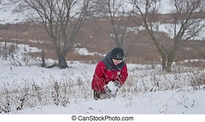 Teen boy rolling a ball of snow to build winter a fortress....