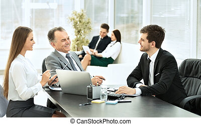 Business partners are discussing a plan of cooperation against the background of team work
