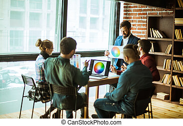 group of creative designers discuss the color palette in a...