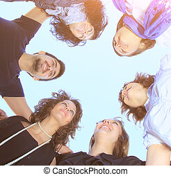 a group of young people in a circle on the sky looking at each other