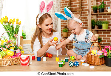 Happy easter! family mother and baby son paint eggs for holiday Easter