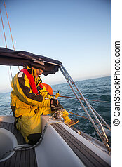 Man Cranking A Winch On Sail Boat In Sea - Mature man...