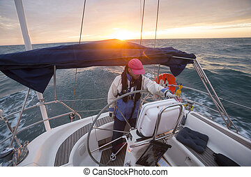 Man Standing At Helm Of Yacht Sailing In Sea During Sunset -...