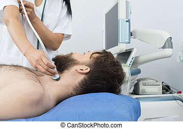 Patient Undergoing Ultrasound Of Thyroid From Doctor - Male...