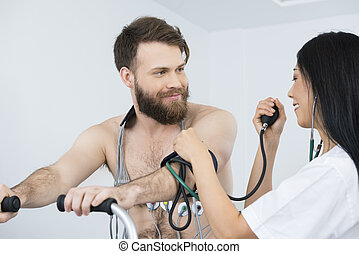 Doctor Measuring Blood Pressure Of Patient With Electrodes...