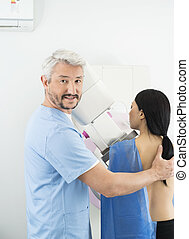 Doctor Assisting Woman Undergoing Mammogram X-ray Test In...