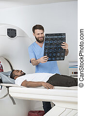 Radiologist Holding X-ray Report While Patient Lying On CT...