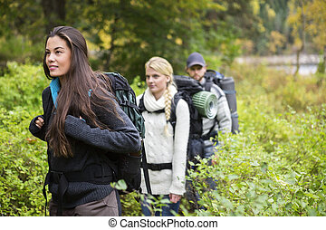 Beautiful Woman Hiking With Friends In Forest - Beautiful...