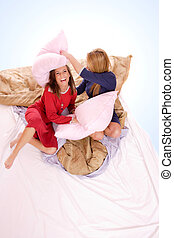 Fighting with pillows in bed - Two beautiful young woman...