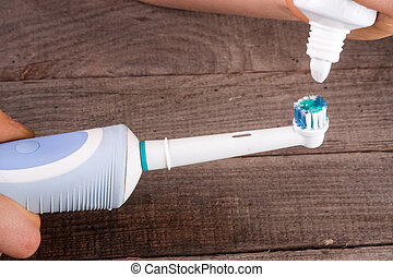 Electric Toothbrush with toothpaste in hand on an old wooden...