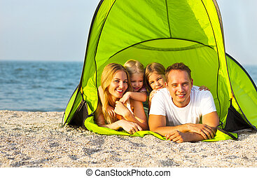 Happy young family camping on the beach. Summertime