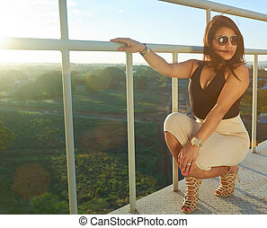 Glamur woman sitting in staircase with gold sunglasses and...