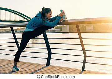 Female athlete streching outdoors by the riverside