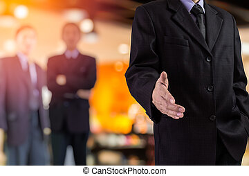 Business handshake and business people concept. Two business men over sunny office background.
