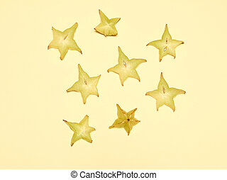 Stacked slices of star fruit or karambole on a yellow...