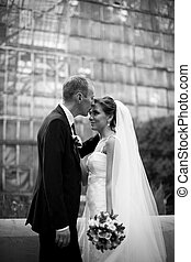 Black and white picture of groom kissing bride's forehead in the garden