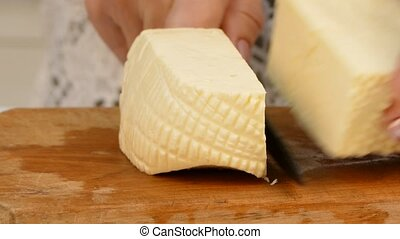 Female hands cutting cheese on the wooden cutting board -...
