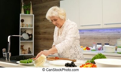 Mature gray-haired woman cut the cherry tomatoes for a salad in the kitchen.