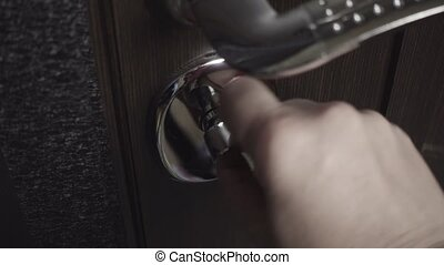 Female hand closes the lock on the door - Female hand closes...