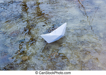 Paper boat in a puddle of melt water - Toy paper boat made...