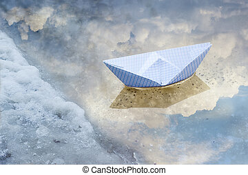 Paper boat in a puddle of water from melted snow - Toy paper...