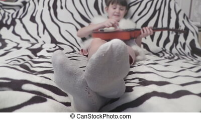 Girl moving her legs in socks in the background with a guitar