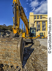 Yellow excavator with shovel and other heavy machine at...