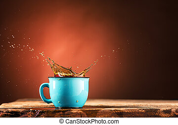 Brown splashes out drink from cup of tea on a brown background