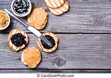 Peanut butter and jam sandwich on rustic wooden background