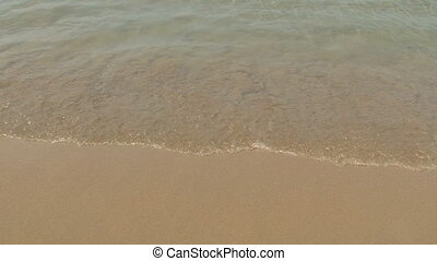 close up scene of soft wave from the sea on sandy beach at sunrise in morning, high definition