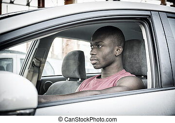 Handsome Young Black Man Driving a Car, wearing red shirt,...