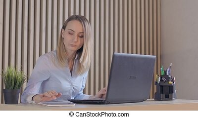 Overwhelmed, sad businesswoman with documents and laptop in...