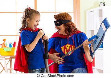 Happy woman and kid prepare for room cleaning. Mother and her child girl playing together. Family in Superhero costumes.