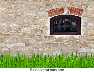 Old stone wall with a small window and a young grass in the...