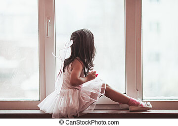 Dreamy girl at the window - Dreamy little girl in a pink...