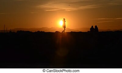 Silhouette of people watching an orange sunset - Silhouette...