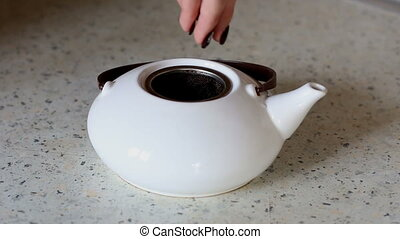putting tea leaves to ketle ceramic teapot and pouring with boiling water