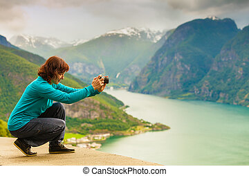 Female tourist taking photo at norwegian fjord - Tourism and...