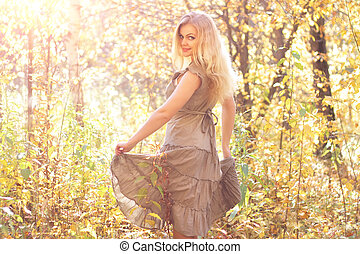 Attractive girl dances in the autumn forest