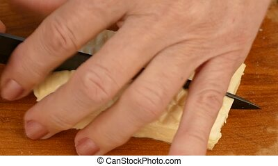 The woman cut the cheese with a knife. - An old woman cuts...